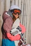 Усмехаясь молодая женщина обнимает сноуборд стоковые фотографии rf