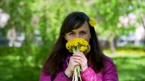Усмехаясь молодая женщина обнюхивая желтые одуванчики сток-видео