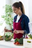 Усмехаясь молодая женщина подготавливая салат в кухне дома Стоковая Фотография RF