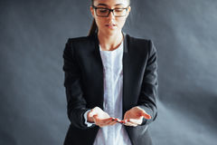 Усмехаясь молодая женщина показывая что-то на ладони обеих рук раскрывает Стоковая Фотография RF