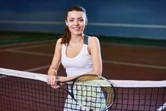 Усмехаясь молодая женщина представляя в теннисном корте стоковое фото rf