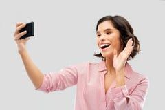 Усмехаясь молодая женщина принимая selfie смартфоном стоковое фото rf