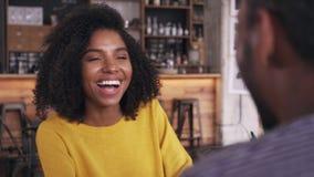 Усмехаясь молодая женщина разговаривая с человеком в кафе сток-видео