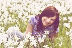 Усмехаясь молодая женщина сидя среди daffodils Стоковые Фото