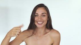 Усмехаясь молодая женщина с длинными волосами и веснушками показывает ` k знака o и большой палец руки вверх с ее пальцами акции видеоматериалы