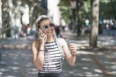 Усмехаясь молодая женщина с умным телефоном стоковая фотография