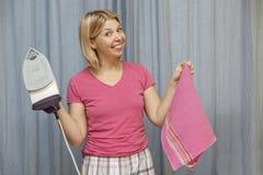 Усмехаясь молодая женщина с утюгом в ее руках стоковая фотография