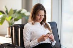 Усмехаясь молодая коммерсантка используя smartphone пока ждущ с стоковое фото
