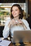 Усмехаясь молодая коммерсантка сидя на кафе внутри помещения стоковая фотография rf