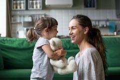 Усмехаясь молодая мама разговаривая с меньшей дочерью стоковые фото