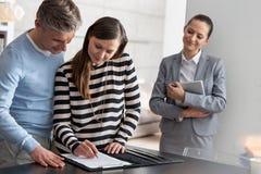 Усмехаясь молодая продавщица смотря контракт подписания женщины пока готовящ человека в квартире стоковые изображения