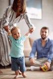 Усмехаясь молодая семья играя и младенец уча идти дома стоковые изображения rf