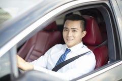 Усмехаясь молодой бизнесмен управляя автомобилем стоковые фотографии rf