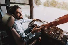 Усмехаясь молодой водитель принимая билет от пассажира стоковая фотография rf