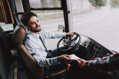 Усмехаясь молодой водитель принимая билет от пассажира стоковое изображение