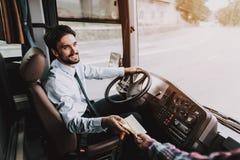Усмехаясь молодой водитель принимая билет от пассажира стоковые фото