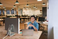 Усмехаясь молодой дизайнер работая на его столе в офисе Стоковая Фотография