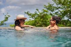 2 усмехаясь молодой женщины в бассейне Стоковая Фотография