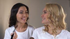 2 усмехаясь молодой женщины кладя вечер составляют и подготавливая для партии, красоты видеоматериал