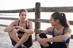 2 усмехаясь молодой женщины сидя на пляже Стоковые Фото