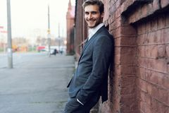Усмехаясь молодой мужской менеджер официальный одел полагаться на стене outdoors стоковое фото