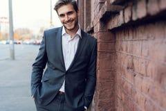 Усмехаясь молодой мужской менеджер официальный одел полагаться на стене outdoors стоковые фотографии rf