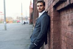 Усмехаясь молодой мужской менеджер официальный одел полагаться на стене outdoors стоковое фото rf