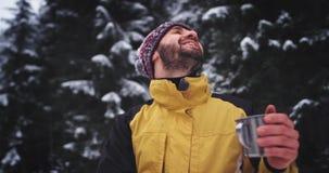 Усмехаясь молодой парень в середине изумительного снежного леса, он очень ликующ полностью ландшафта он видит, кстати он сток-видео