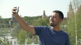 Усмехаясь молодой турист принимая selfie с его телефоном в Москве, России сток-видео