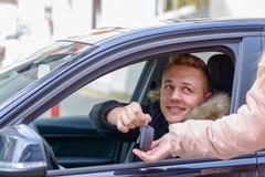 Усмехаясь молодой человек в автомобиле вручая над его ключами Стоковая Фотография