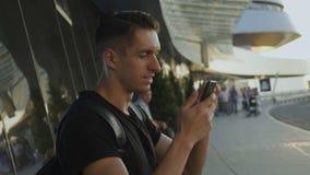 Усмехаясь молодой человек в черной футболке используя его смартфон, запись на ленту и скроллинг На аэропорте или автовокзале видеоматериал