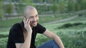 Усмехаясь молодой человек сидя в парке с сумкой на заднем плане растительности и говоря на телефоне видеоматериал