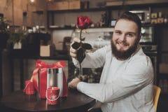 Усмехаясь молодой человек сидя таблица держа розу стоковое фото rf