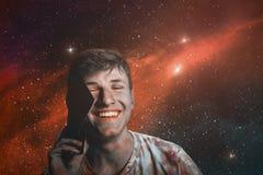 Усмехаясь молодой человек счастливого подростка говоря на мобильном телефоне против стоковое изображение rf