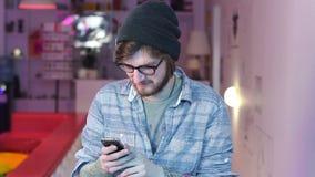 Усмехаясь молодой человек читает смеяться над фото сообщений мобильного телефона сток-видео