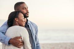 Усмехаясь молодые африканские пары наслаждаясь заходом солнца на пляже Стоковые Изображения