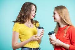 Усмехаясь молодые женщины выпивая кофе и говорить люди, сообщение и приятельство Стоковые Фото