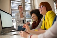 Усмехаясь молодые женщины в деятельности офиса стоковое изображение
