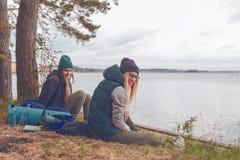 Усмехаясь молодые женщины отдыхая во время путешествовать около озера стоковые изображения rf