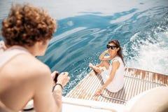 Усмехаясь молодые пары держа стекла с напитком пока путешествующ на яхте стоковые изображения