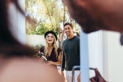 Усмехаясь молодые пары на входной двери с бутылкой вина Стоковые Фотографии RF