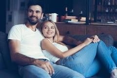 Усмехаясь молодые пары ослабляя и смотря ТВ дома Стоковая Фотография