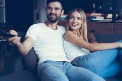 Усмехаясь молодые пары ослабляя и смотря ТВ дома Стоковые Фотографии RF