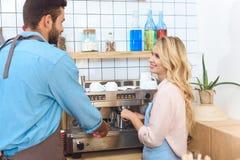 усмехаясь молодые пары работников кафа делая кофе совместно и использование Стоковая Фотография