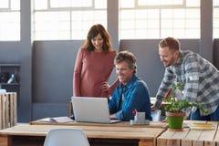Усмехаясь молодые сотрудники используя компьтер-книжку совместно в офисе Стоковое фото RF