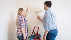 Усмехаясь молодые стены картины пар в новом доме Стоковые Фотографии RF