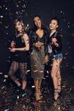 Усмехаясь молодые стильные женщины держа бутылки и partying стоковое изображение