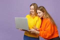 2 усмехаясь молодых белокурых девушки сестер близнецов в ярком красочном удерживании одежд, используя компьютер ПК ноутбука изоли стоковые изображения rf