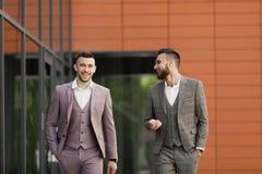 2 усмехаясь молодых бизнесмена идя и говоря в городе Стоковые Фотографии RF