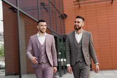 2 усмехаясь молодых бизнесмена идя и говоря в городе Стоковые Фото